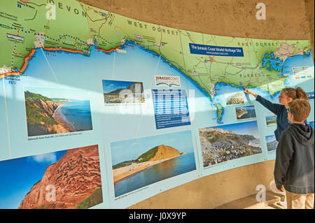 Two children looking at a map of Dorset's Jurassic Coast - Stock Image