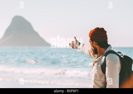 Man traveler showing rock in the ocean enjoying landscape travel healthy lifestyle adventure summer vacations in Norway active trip outdoor - Stock Image