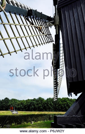 Black wooden windmill with cannon in distance at Vesting Bourtange, the star-shaped fortress in Groningen Province, The Netherlands - Stock Image
