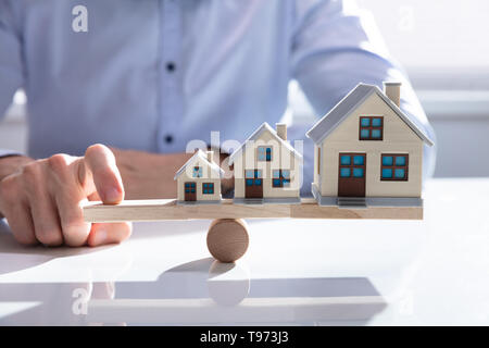 Parsons Hand Balancing Growing House Models On Wooden Seesaw - Stock Image