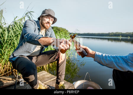 Two male friends clinking beer bottles sitting together during the fishing process on the pier near the lake - Stock Image