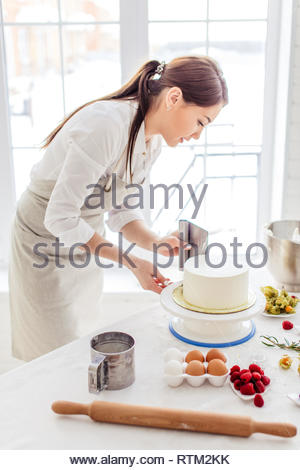 hardworking girl giving smooth edges to cake, close up side view photo. - Stock Image
