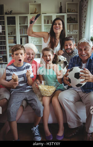 Happy multi-generation family watching soccer match on television in living room - Stock Image