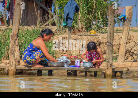 Mother and daughter washing clothes in front of their home, Inle Lake Myanmar - Stock Image