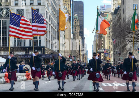 New York City, USA. 16th Mar, 2019. People walk with Irish and American flags during St. Patrick's day parade along 5th Avenue. Credit: jbdodane/Alamy Live News - Stock Image