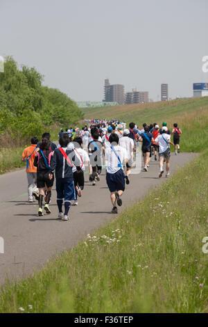running marathon green grass runners - Stock Image