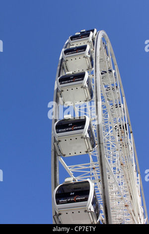 WIDE VIEW OF A EMPTY WHITE FERRIS WHEEL AGAINST BLUE SKY BACKGROUND BDB - Stock Image