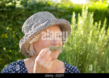 Senior woman in blue polka-dotted dress and straw hat sitting in her garden and enjoying the intense fragrance of - Stock Image