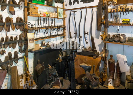 Clogmakers workshop showing the workbench with several anvils tools and clogs  at the Ryedale Folk Museum in Hutton le Hole North Yorkshire England UK - Stock Image