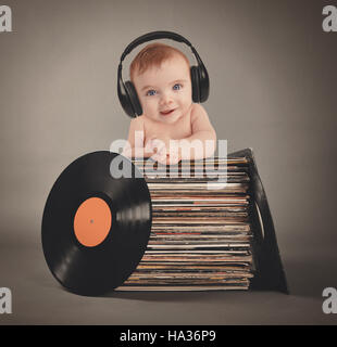 A little baby is wearing music headphones with retro vinyl records on an isolated gray background for a party or - Stock Image