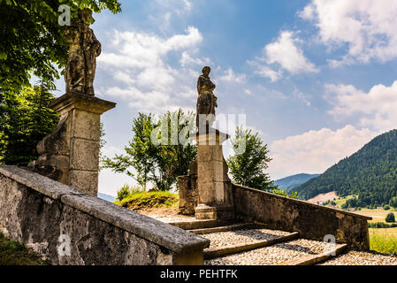Church steps and statues at Pieve Tesino, Trentino, Italy - Stock Image