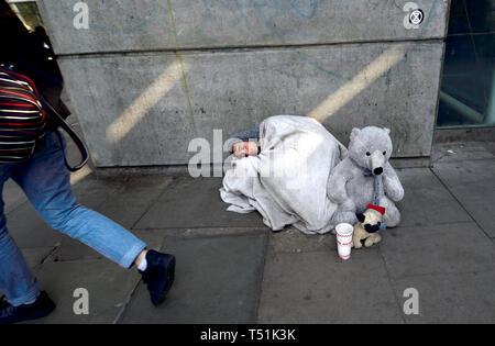 London, England, UK. Homeless man on the South Bank, asleep with a teddy bear - Stock Image