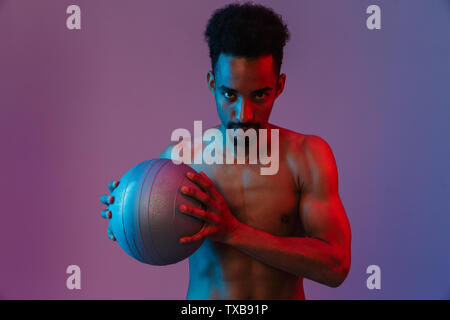 Portrait of young sporting shirtless african american man poising with fitball isolated over violet background - Stock Image