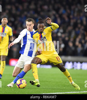 Solly March of Brighton tackles Wilfred Zaha of Crystal Palace during the Premier League match between Brighton & Hove Albion and Crystal Palace at the Amex Stadium . 04 December 2018 Photograph taken by Simon Dack  Editorial use only. No merchandising. For Football images FA and Premier League restrictions apply inc. no internet/mobile usage without FAPL license - for details contact Football Dataco - Stock Image