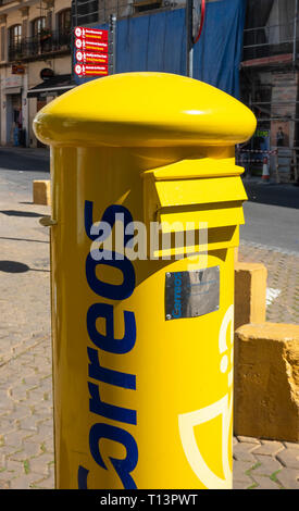 A yellow Correos letterbox in Seville, Spain - Stock Image