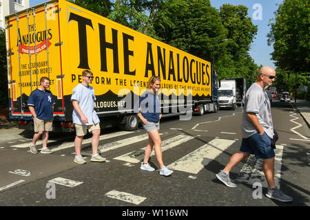 Abbey Road, London, UK.  29th June 2019.  UK Weather:  Tourists crossing the famous Abbey Road zebra crossing made famous by The Beatles on a scorching hot day in London.  A lorry is parked on the road which has advertising on it for 'The Analogues' Beatles musical.  Picture Credit: Graham Hunt Photography. Credit: Graham Hunt/Alamy Live News - Stock Image