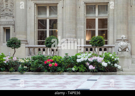 Courtyard flowers at entrance to bank building at Place Vendome, Paris, France - Stock Image
