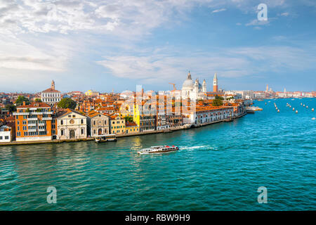 A Venice, Italy water taxi cruises the grand canal with the dome of Santa Maria Della Salute Cathedral, the Campanile and St. Mark's square in view - Stock Image