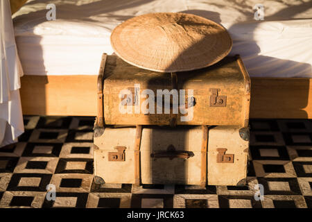 Classic vintage iron box and bamboo hat in cottage - Stock Image