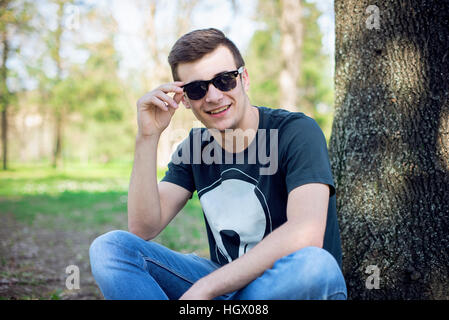 Young man relaxing in the park on a summers day - Stock Image