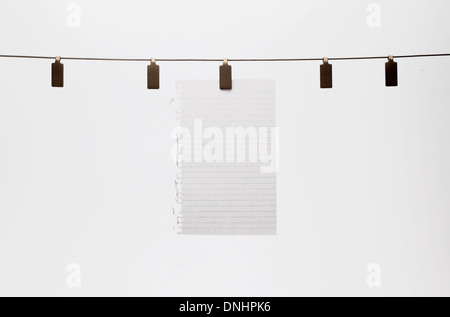 A blank piece of paper hanging with a clip to a straight wire. White background - Stock Image