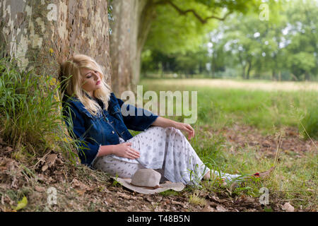 Beautiful young blonde woman sitting against a huge tree in a park in summertime - Stock Image