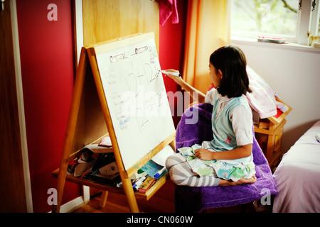 Girl writes maths problems on whiteboard. - Stock Image