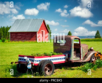 Old truck with flowers and barn. Near flora, Oregon - Stock Image