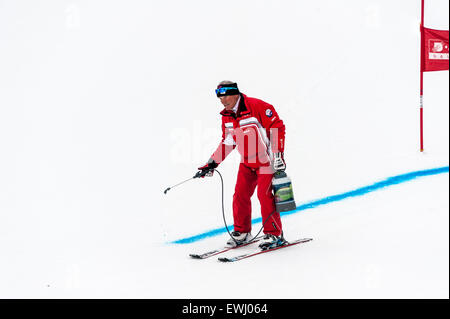 A course marshal marking the ski piste with blue dye before a giant slalom race. A race gate in the background. - Stock Image