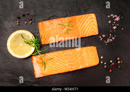Raw salmon with spices on a black background. Two slices of fresh fish, shot from the top with lemon, rosemary, salt, and pepper - Stock Image