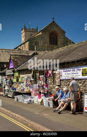 UK, Cumbria, Hawkshead, customers sat outside in sunshine outside gift shop below St Michael and All Angels Parish Church - Stock Image