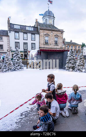 Fake snow turns the Scottish Borders town of Kelso into a Christmas scene for a TV advertisement for Marks & Spencer - children with the artificial sn - Stock Image