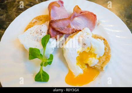 Breakfast snack in Yorkshire a toasted muffin with two slices of fried bacon and two soft poached eggs one cut open - Stock Image