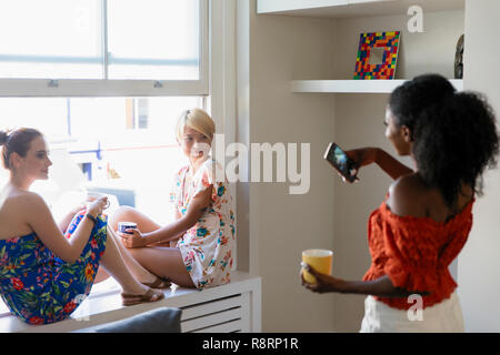 Young woman with camera phone photographing friends sitting in apartment window - Stock Image
