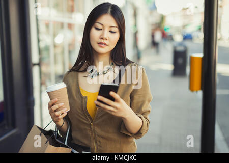 Young woman with coffee texting with cell phone on urban sidewalk - Stock Image