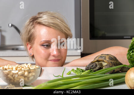Woman stares at tortoise eating salad - Stock Image