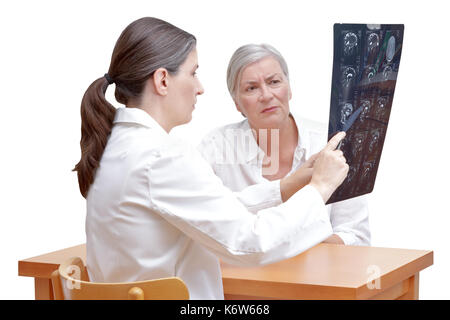 Female middle aged doctor showing her senior patient an mri of her head, isolated on white background - Stock Image