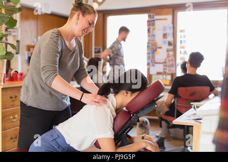 Creative businesswoman receiving massage from masseuse in office - Stock Image