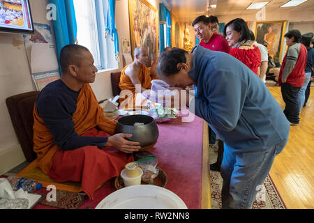 Devout Buddhist worshippers participate in the ancient ritual of feeding the monks. At a temple in Elmhurst, Queens, New York City. - Stock Image