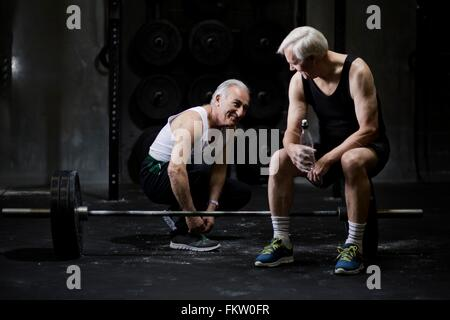 Senior men chatting and tying trainer laces in dark gym - Stock Image