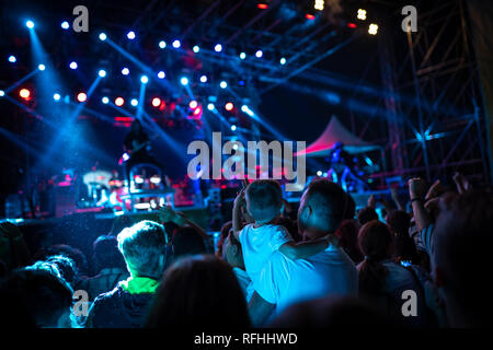 Young boy and his family attending a concert and rising hands in the air - Stock Image