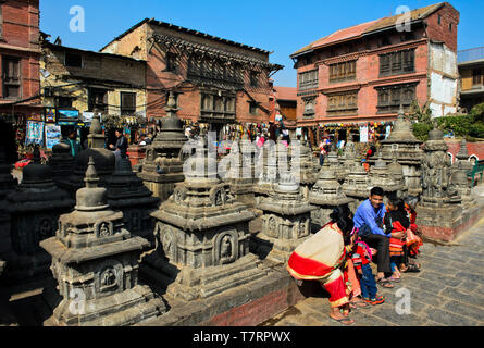 Local family in colorful dresses resting on a square with stupas on the site of the Swayambhunath temple or Monkey Temple, Kathmandu, Nepal - Stock Image