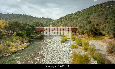 Side view of the bridgeport Covered Bridge at South Yuba River in California, USA, featuring the fall colors in the river. This bridge has the longest - Stock Image