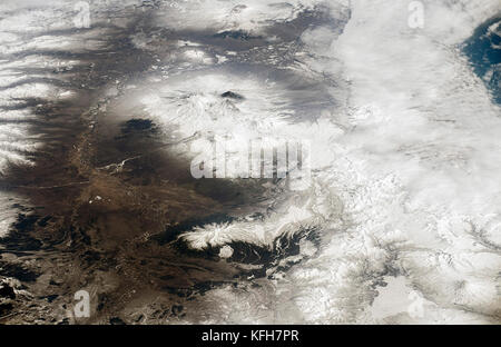 Photo of snow capped volcanoes in Kamchatka, Russia from the International Space Station. The three volcanoes visible - Stock Image