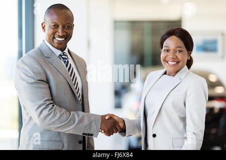 beautiful African woman handshaking with car dealer - Stock Image