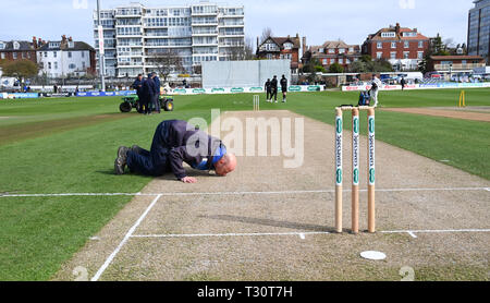 Hove Sussex, UK. 05th Apr, 2019. One of the Sussex groundsmen Marc Gravett kisses the wicket on his last day working at the club before the Specasavers County Championship Division Two match between Sussex and Leicestershire at the 1st Central County Ground in Hove on a sunny but cool first morning of the season Credit: Simon Dack/Alamy Live News - Stock Image