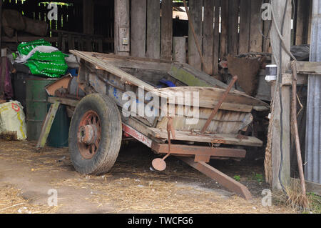 Old wooden farm shed with derelict cart and old drum, bags and tools. Purbeck. Dorset - Stock Image