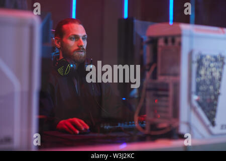 Serious young bearded software engineer in black hoodie sitting at table and creating web design on computer - Stock Image