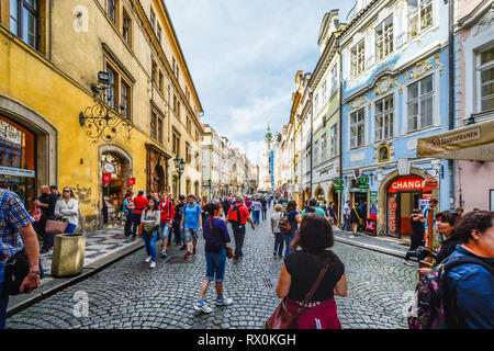 Tourists crowd the King's Way through Male Strana enjoying shops and cafes on the way to the Prague Castle Complex with St Nicholas church in view - Stock Image
