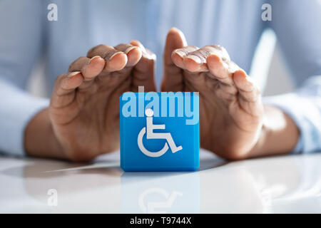 Close-up Of A Human's Hand Protecting Blue Cubic Block With Disabled Handicap Icon - Stock Image